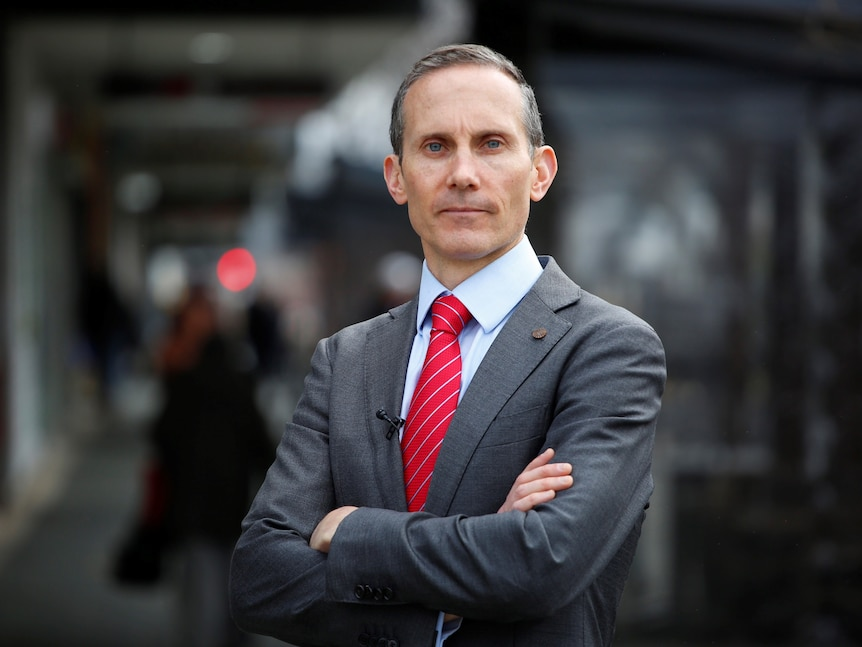 Andrew Fenner wearing a suit and red tie with his arms crossed