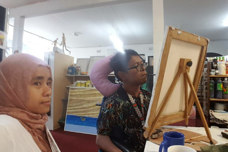 Faisal Rusdi paints with his mouth as his wife Cucu Saidah looks on.