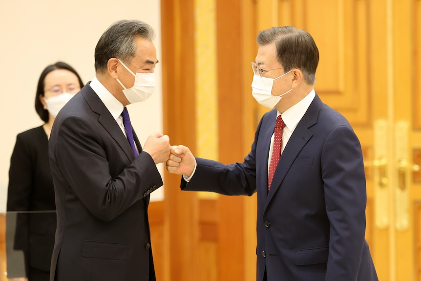 South Korean President Moon Jae-in, right, greets Chinese Foreign Minister Wang Yi