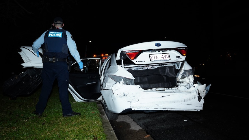 A police officer stands next to a smashed white sedan.