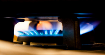 Gas flame burns on stove, close up.