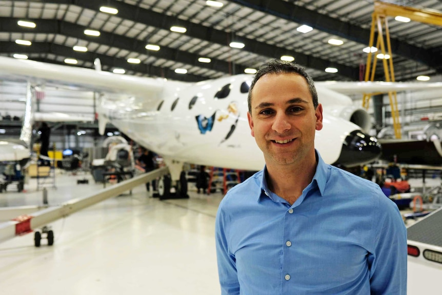 Enrico Palermo stands in front of a hangar full of spaceships