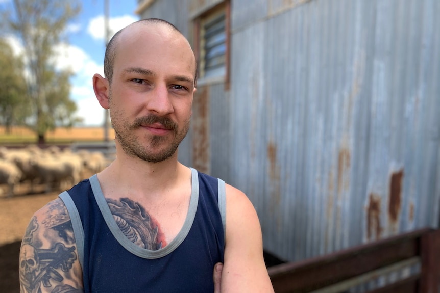 Male shearer with tattoos standing in front of shed