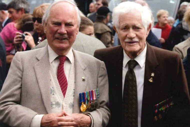 Two old men in suits, ties and a row of war medals smile for a photo with a crowd behind them.