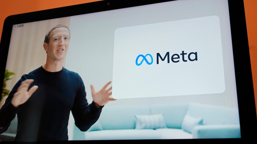 A screen shows a man in a black long sleeve top using his hands to explain a new concept, called Meta.