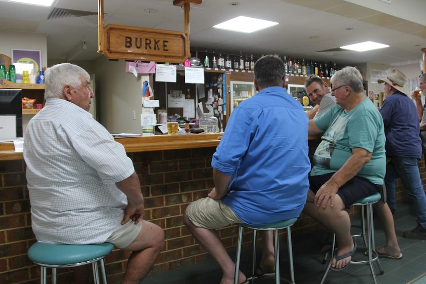 men in summer clothes sitting in country pub at bar