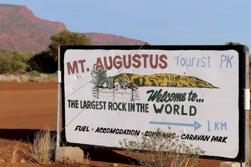 A sign reading 'Mt Augustus Tourist Park' with a big red rock in the background.