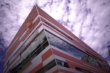A building clad in silver and dark red, photographed from below looking towards the sky