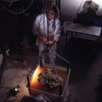 A woman in a dark room stands above a rock she's about to dip a bucket.