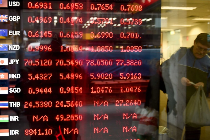A man leaves a bank next to an electronic screen displaying currency rates in red.