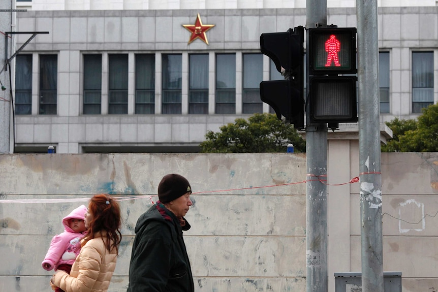 Locals walk in front of 'Unit 61398', a secretive Chinese military unit, in the outskirts of Shanghai.