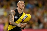 A Richmond Tigers AFL player handballs with his right hand.