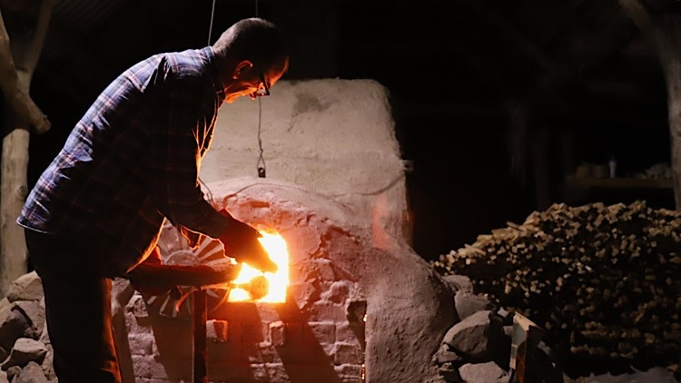 A man stands next to a woodfired kilm with a fire blazing, as he tends to pottery objects.