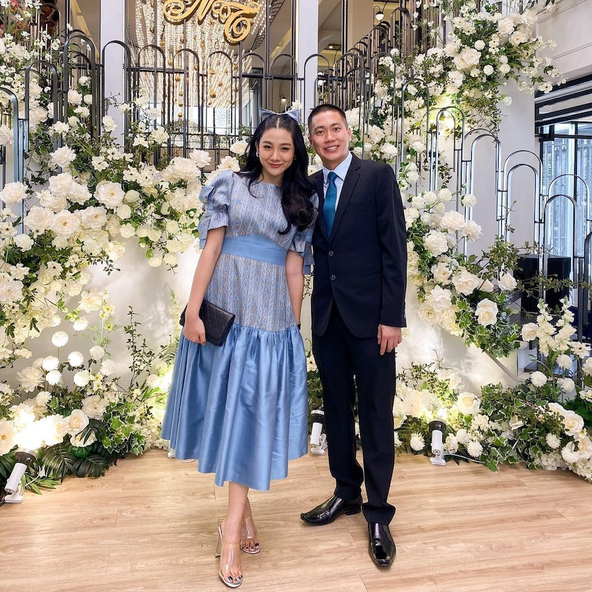 A Thai woman in a long blue dress and a man in a suit stand together surrounded by white flowers in a home