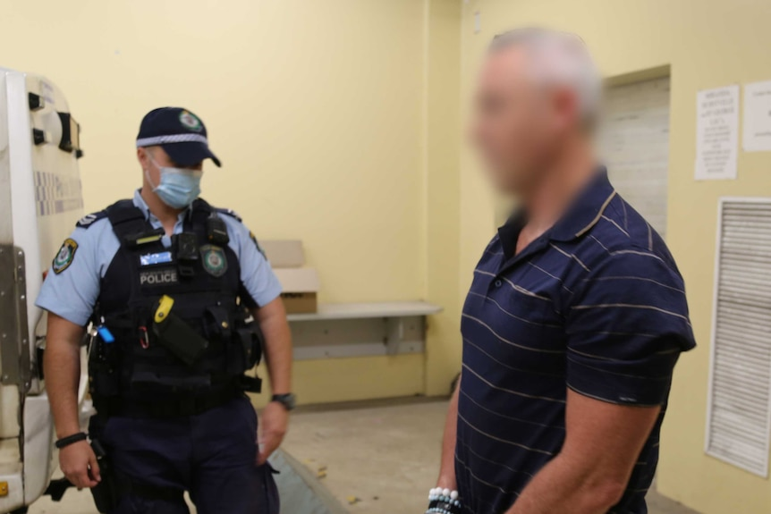A police officer wearing a mask stands next to a man with a blurred face.