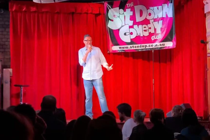Vikesh holds a microphone as he stands on stage at a stand-up comedy event.