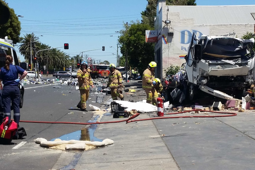 Fire crews work at the scene of the explosion, with the damaged truck in shot and debris across the road.