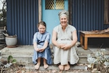 Allison Davies with her daughter Maple outside her home,smiling to the camera