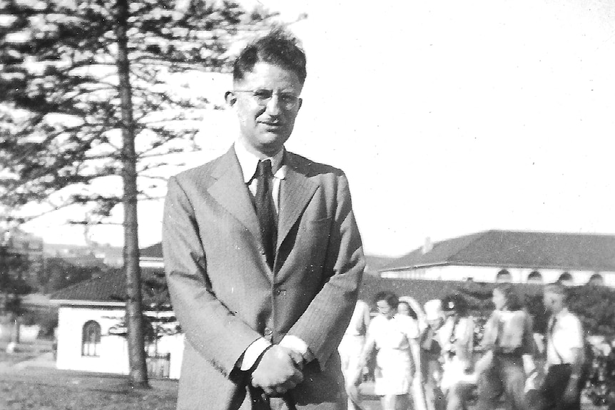 A black and white photo of a man wearing a suit standing in front of a group of women.