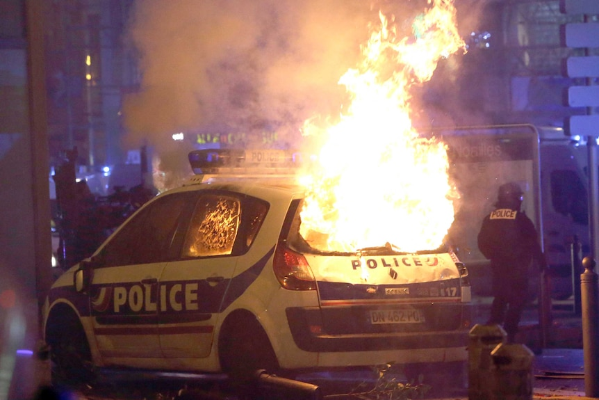 A large fire consumes a French police car during protests.