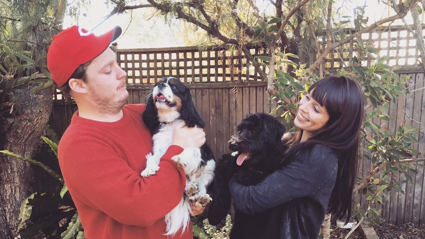 A couple in a backyard with two dogs in their arms.