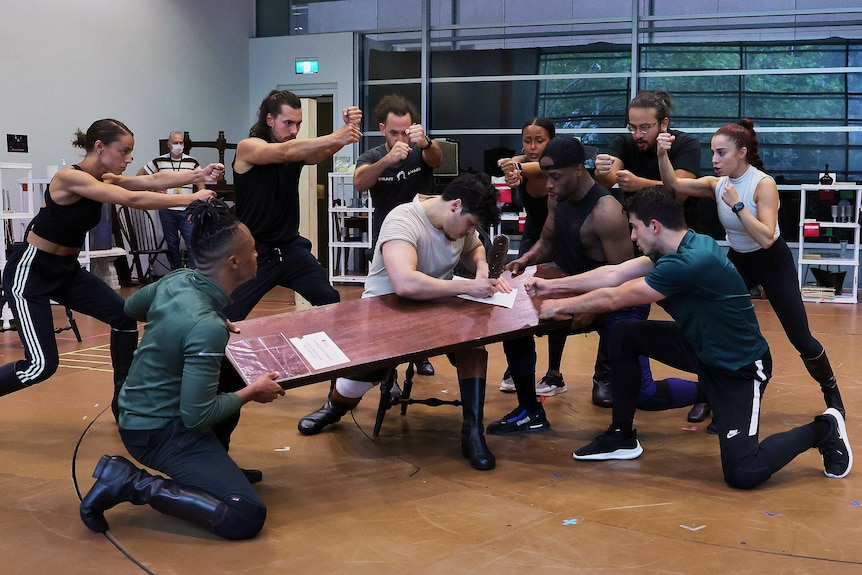 A group of people dance around a man writing on a plank of wood in a rehearsal studio.