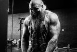 An extremely muscular man lifts weights.
