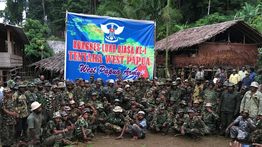 West Papua separatist groups gather below an army banner.