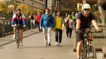 Cyclists and pedestrians move along the footpath beside the Yarra River in Southbank.