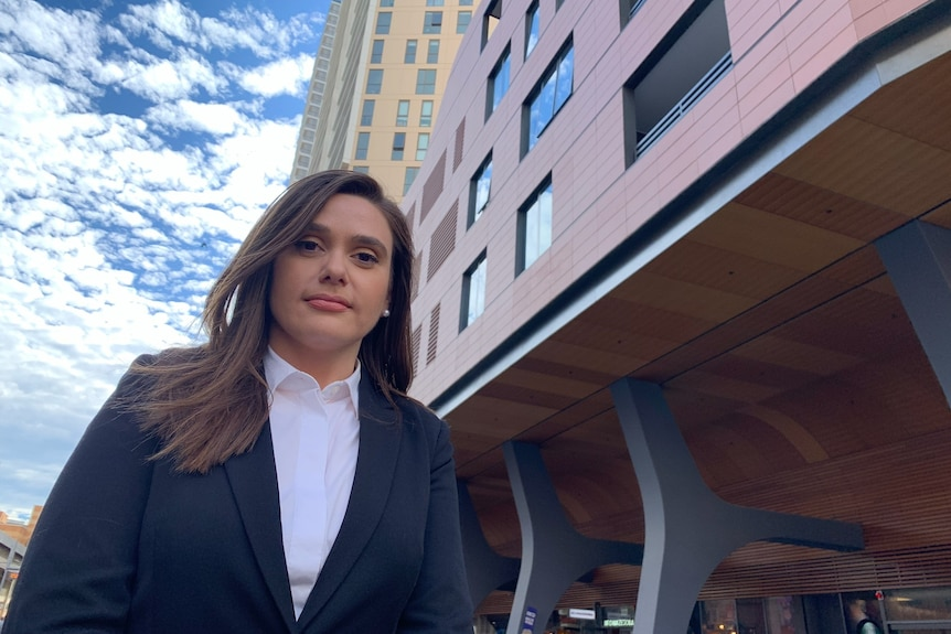 Woman in dark blazer and white blouse stands in front of an office building.