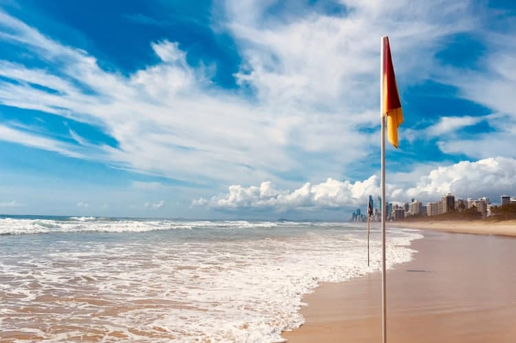 A beach with no people showing a lifesaving pole with high-rise buildings in the distance