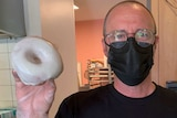 A man in a black face mask holds a white-iced doughnut with a gloved hand.