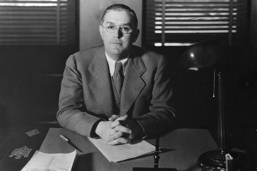 Film censor Joseph Breen sitting in his office in 1935, black and white.