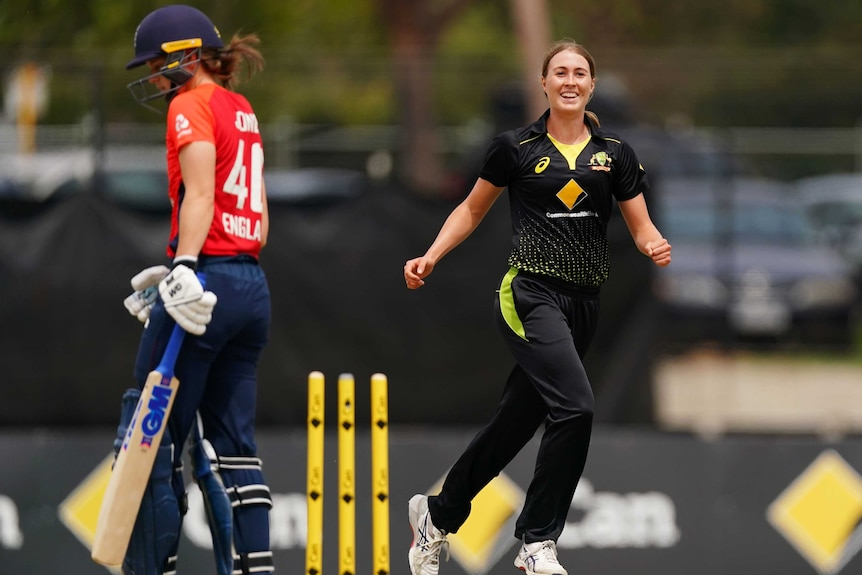 A smiling female fast bowler celebrates a clean-bowled ODI wicket as the batter walks off.