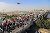A wide shot shows hundreds of protestors walking down an Iranian street
