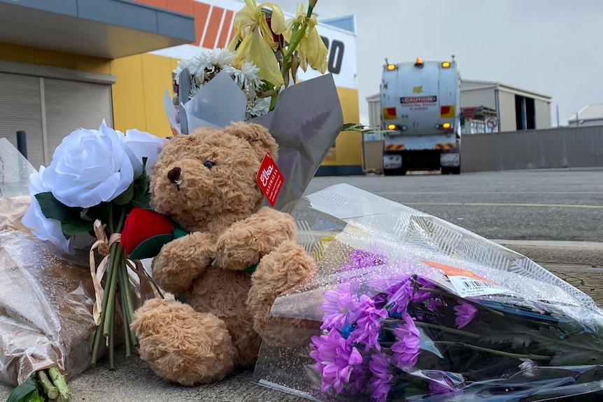 A teddy bear and flowers with a garbage truck parked behind