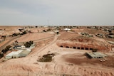 Houses dot along small rolling red dirt hills against a blue-grey background