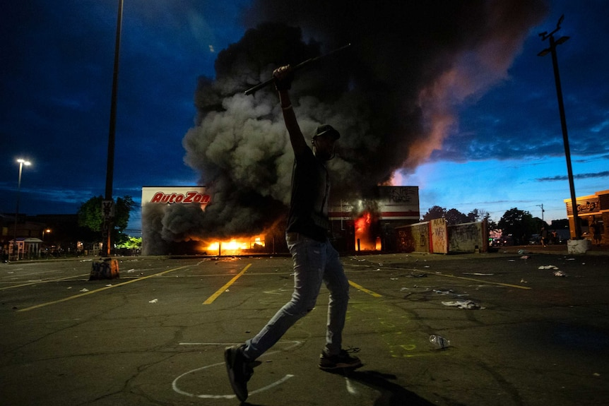 A man poses for a photo in the parking lot in front of a burning building.