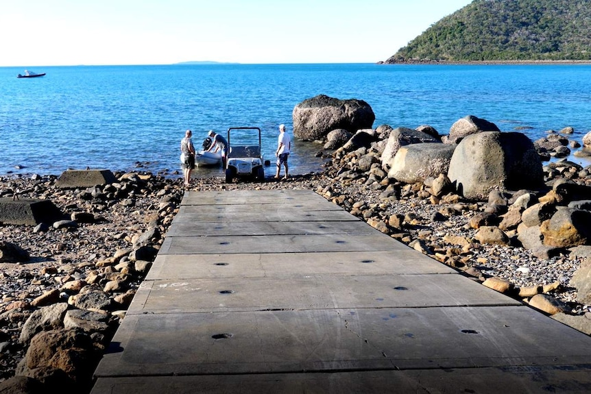 a cement boat ramp leading into the ocean, with men putting a boat in