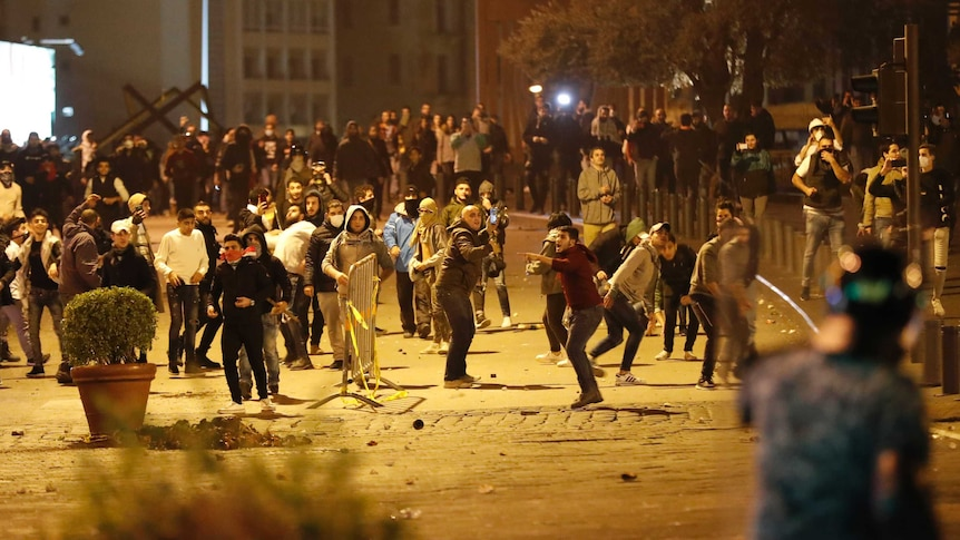 A large group of protesters are gathered across a road and are throwing items