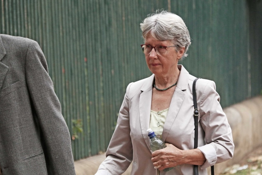 A woman with short grey hair walks while wearing a pale blazer and carrying a water bottle.