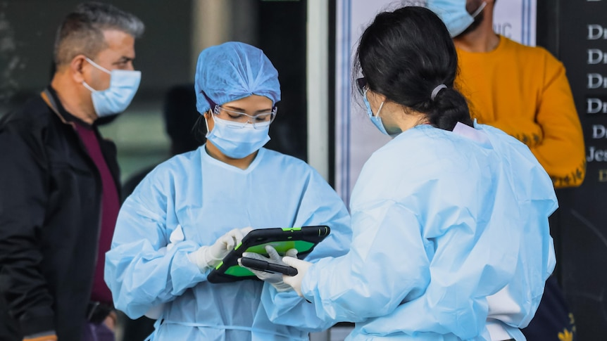 two women wearing protective clothing looking at a tablet