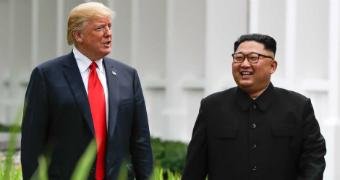 Donald Trump and Kim Jong-un walk together.