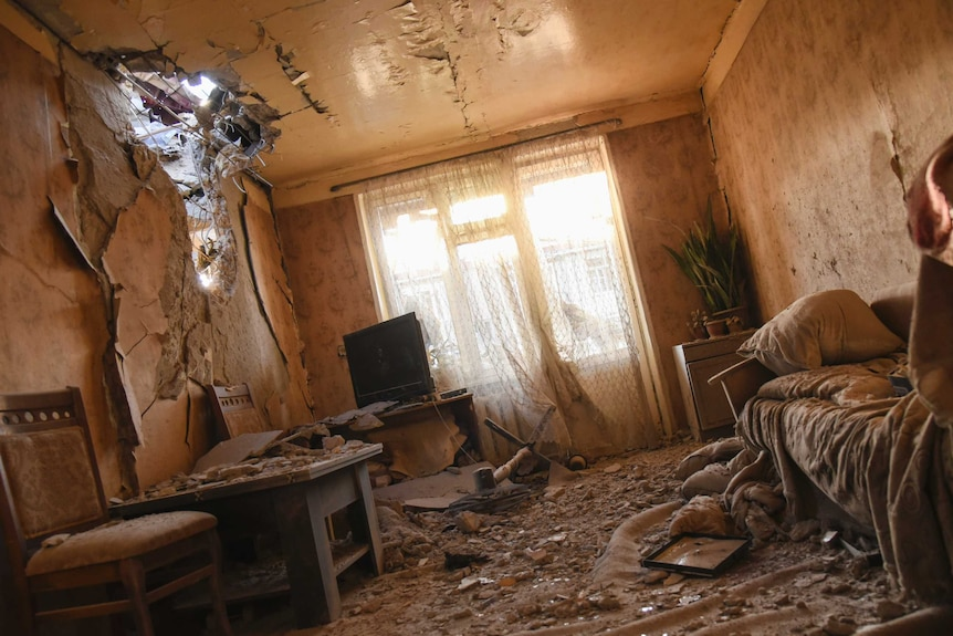 The interior of an apartment where light streams through a hole in the wall, with broken glass and rubble on the floor.