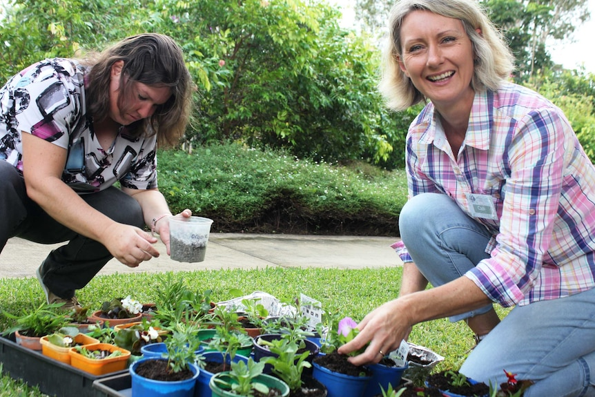 Volunteer Allira and horticultural therapist Cath Manuel put the finishing touches on the seedlings.