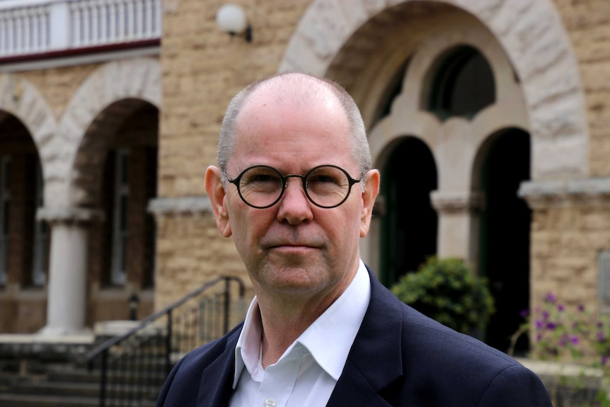 A balding man wearing circular glasses stands in front of a heritage-style sandstone building.