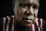 Archie Roach is wearing a striped shirt and sitting under dim lights. He is looking down and his expression is serious.