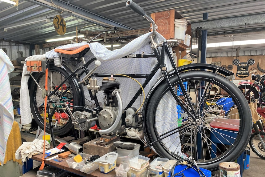 A very old motorbike sits in a shed on a work bench.