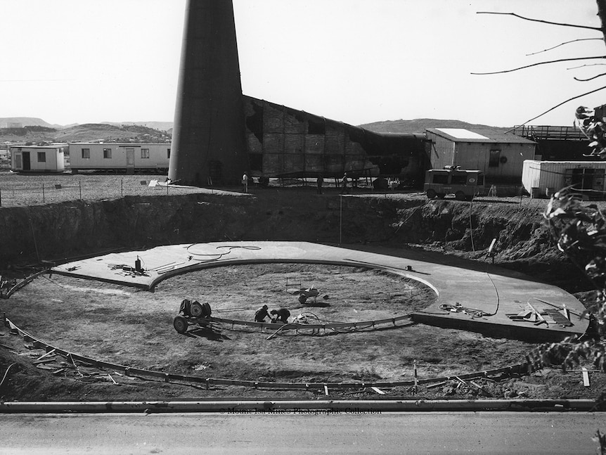 A large circular area of concrete being laid in the ground.