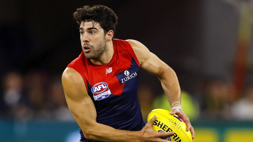 A Melbourne Demons AFL player holds the ball in two hands in the grand final